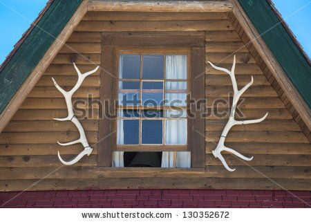 stock-photo-elk-antlers-as-design-feature-on-log-cabin-130352672